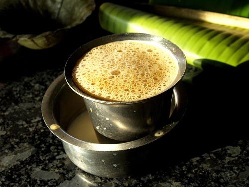 Kaapi, miền Nam Ấn Độ Khi nhìn thấy tách và chiếc đĩa sâu bằng kim loại cùng với dung dịch đậm đặc ở Kerala và Tsmil Nadu, bạn chắc chắn sắp được thưởng thức tách cà phê ngon tuyệt. Dân địa phương trồng cà phê ở miền Nam Ấn Độ, sau khi thu hoạch sẽ rang hạt lên rồi nghiền mịn. Cà phê được pha trong một bình lọc bằng kim loại, trộn với sữa nóng và đổ thẳng vào cốc từ trên cao xuống để tạo bọt. Ảnh: flickr